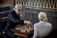Old stylish couple playing chess, marble estate room, classic look,