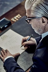 gentleman writing letter, stylish office setting, classic stationary